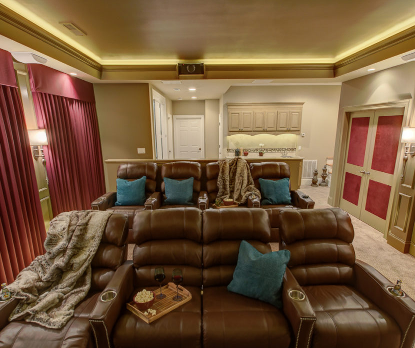 basement home theater room with brown couches