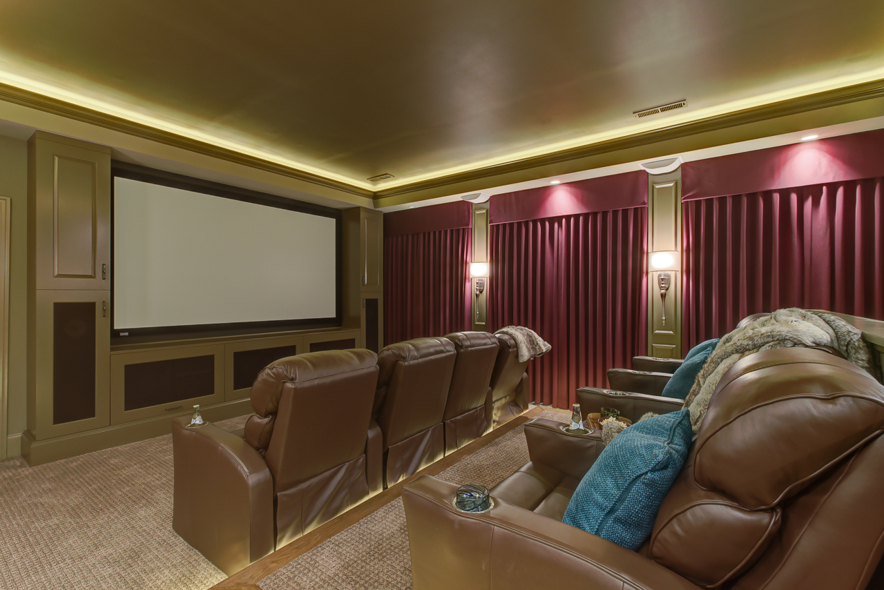 lighted movie theater room with cozy blankets and pillows