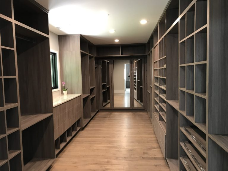large walk in closet with wood shelving