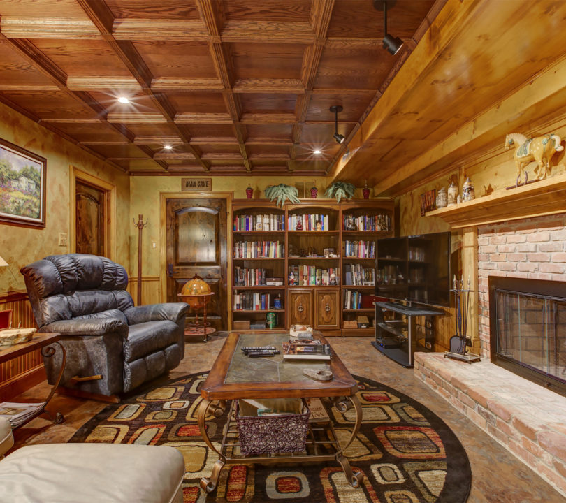 cozy man cave with small library and leather recliner