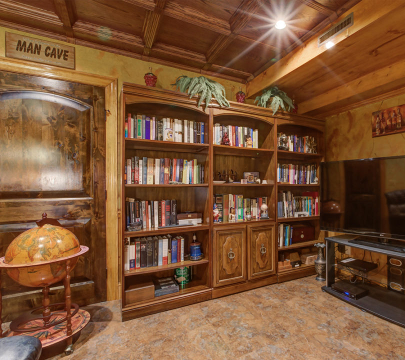 man cave basement with wooden bookshelves and ceiling