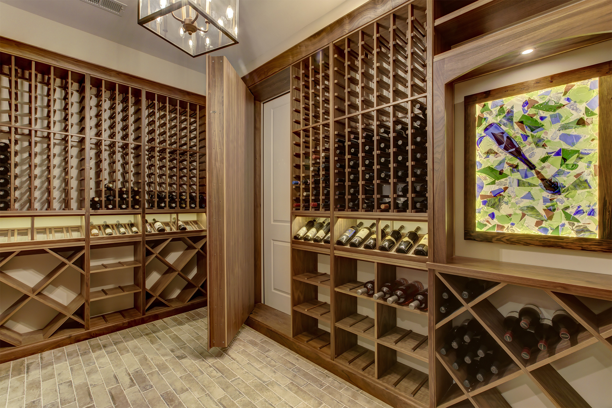 wine storage area with artwork and chandelier