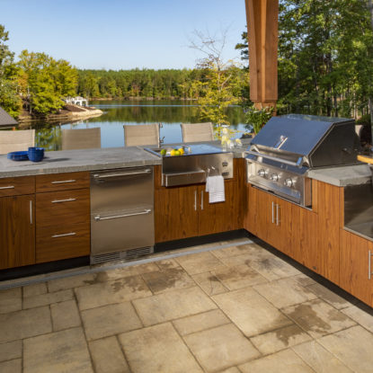 outdoor kitchen with lake view and wood cabinets