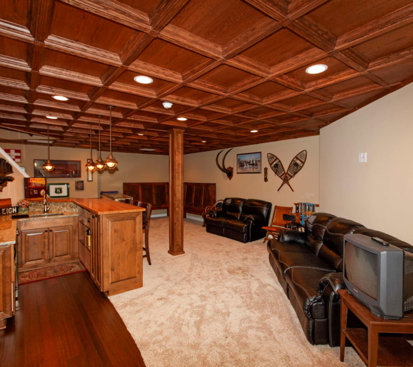 basement with wood panel cieling and bar area